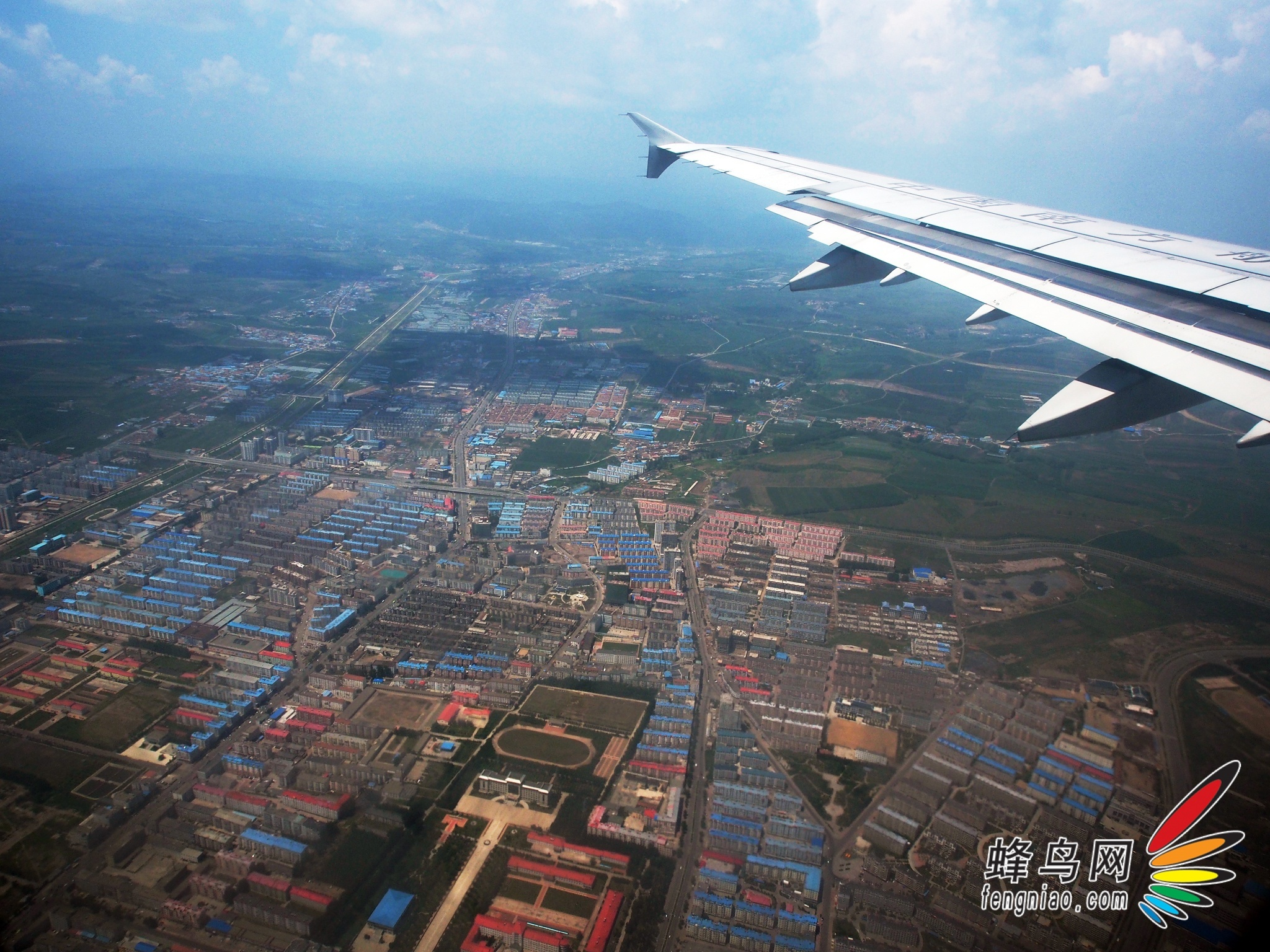 从北京到延吉   去长白山旅行,飞机是最方便快捷的方式。从北京到延吉每天10:30有一趟直飞航班,时长大约两小时。到达延吉机场后,行者还需要乘车4个多小时才能到达长白山景区。  起飞前准备好航拍用的E-M5及两支镜头12-50/F3.5-6.3与75-300/f4.8-6.7  飞机在北京上空   起飞前,北京天空一直阴沉沉的,其实不知道是雾、还是霾,反正空气非常的糟糕。飞机起飞后穿过云雾,顿时天空湛蓝了很多。当飞机飞行平稳后,用E-M5进行了航拍,还好,飞机窗户比较干净,拍摄的蓝天效果很